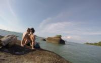 Sitting on a rock at Black Sand Beach, Langkawi, Malaysia