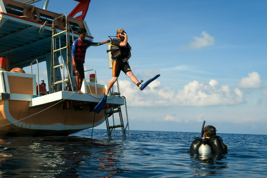 Plunging into the ocean in full scuba diving gear near Koh Tao