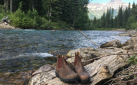Blundstone boots placed on a log near the river in Glacier National Park