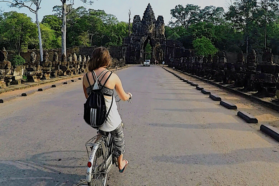 Biking through the West gate at Angkor Wat, Siem Reap, Cambodia
