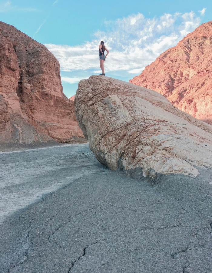 Standing on top of a large rock in Mosaic Canyon